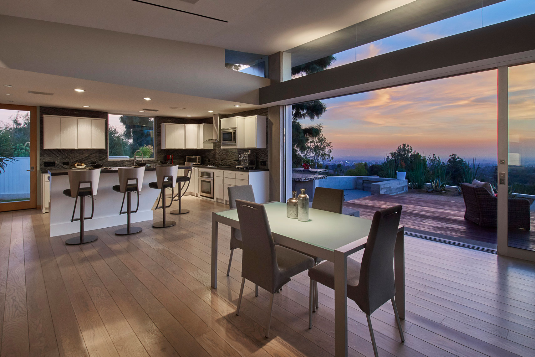 Architectural-photography-of-dining-room-and-kitchen-of-contemporary-Los-Angeles-home-with-open-sliding-glass-door-to-deckatsunset-Joe-Atlas-architectural-photographer-Los-Angeles.