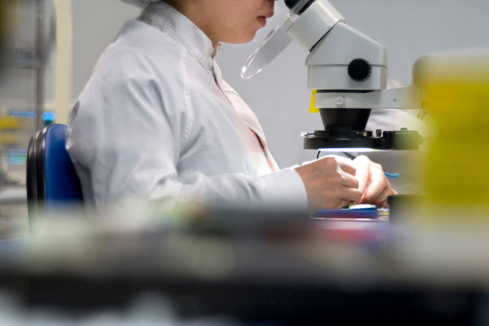 Environmental-portrait-photograph-of-electronics-manufacturing-clean-room-worker-examines-circuitry-under-microscope