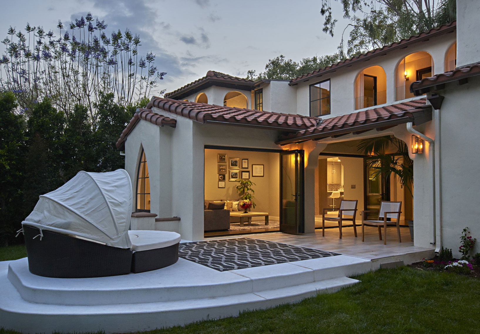 Exterior-of-spanish-style-contemporary-home-with--folding-glass-doors-at-dusk