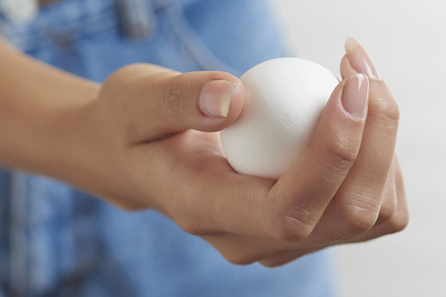 Female-hand-holding-fresh-white-egg-by-Joe-Atlas-food-photography.