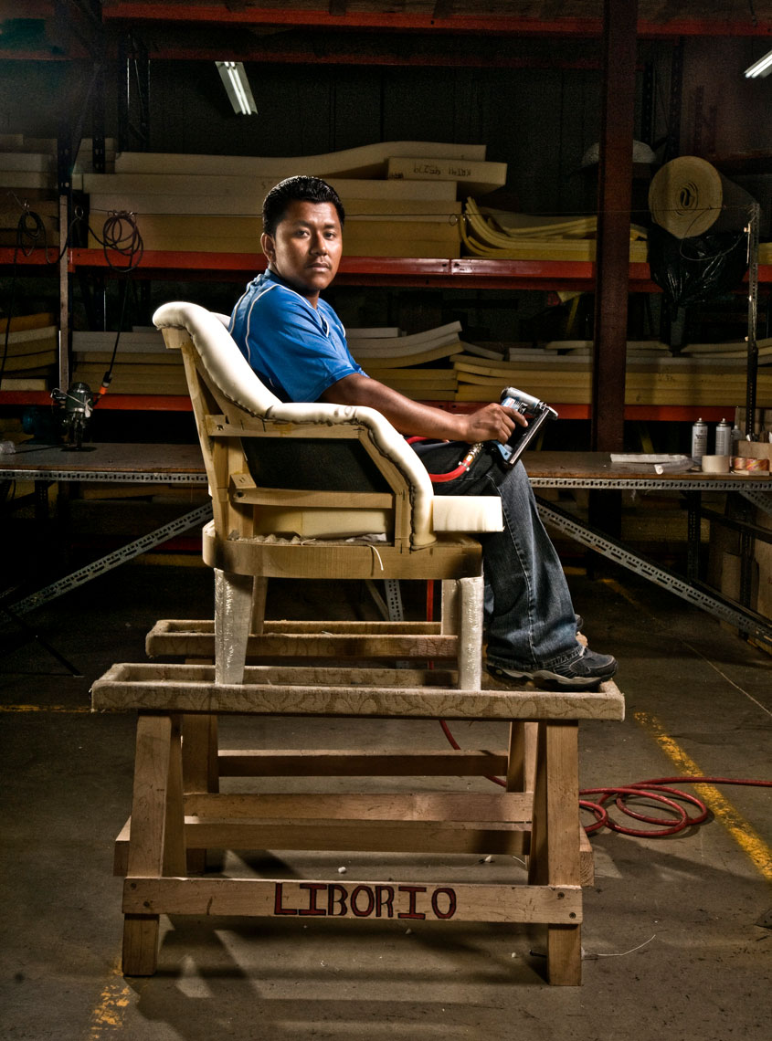 Furniture-and-upholstery-factory-worker-sitting -on-unfinished-wood-chair-frame-by-environmental-portrait-photographer-Joe-Atlas.