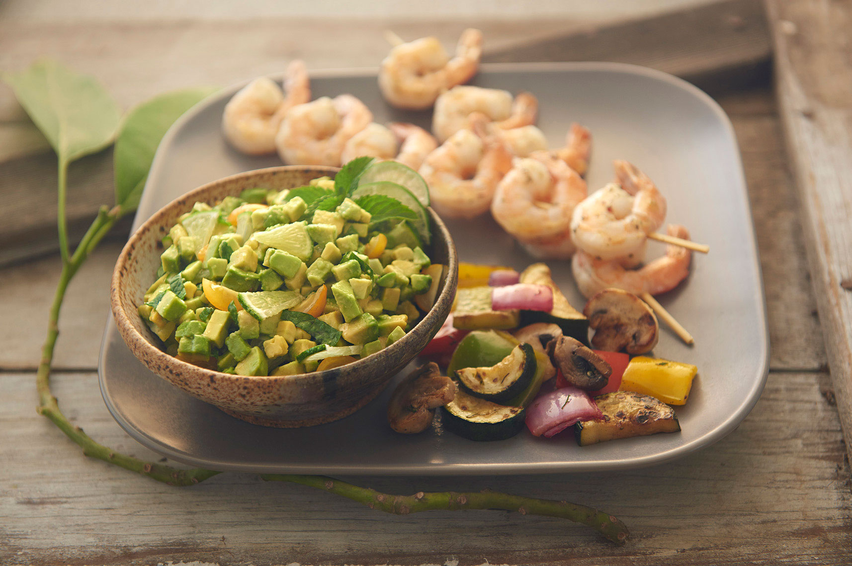 Beautiful-food-photography-of-grilled-shrimp-skewers-and-summer-vegetables-with-mint-lime-avocado-relish
