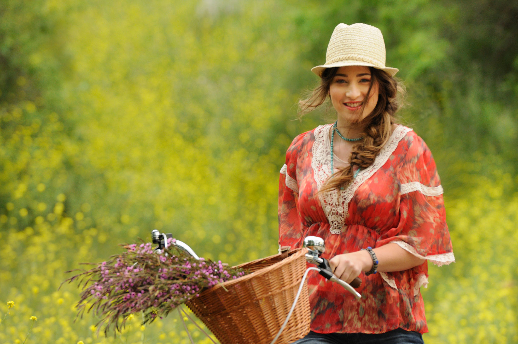 Lifestyle-portrait-of-young-woman-on-a-bike-with-basket-of-flowers
