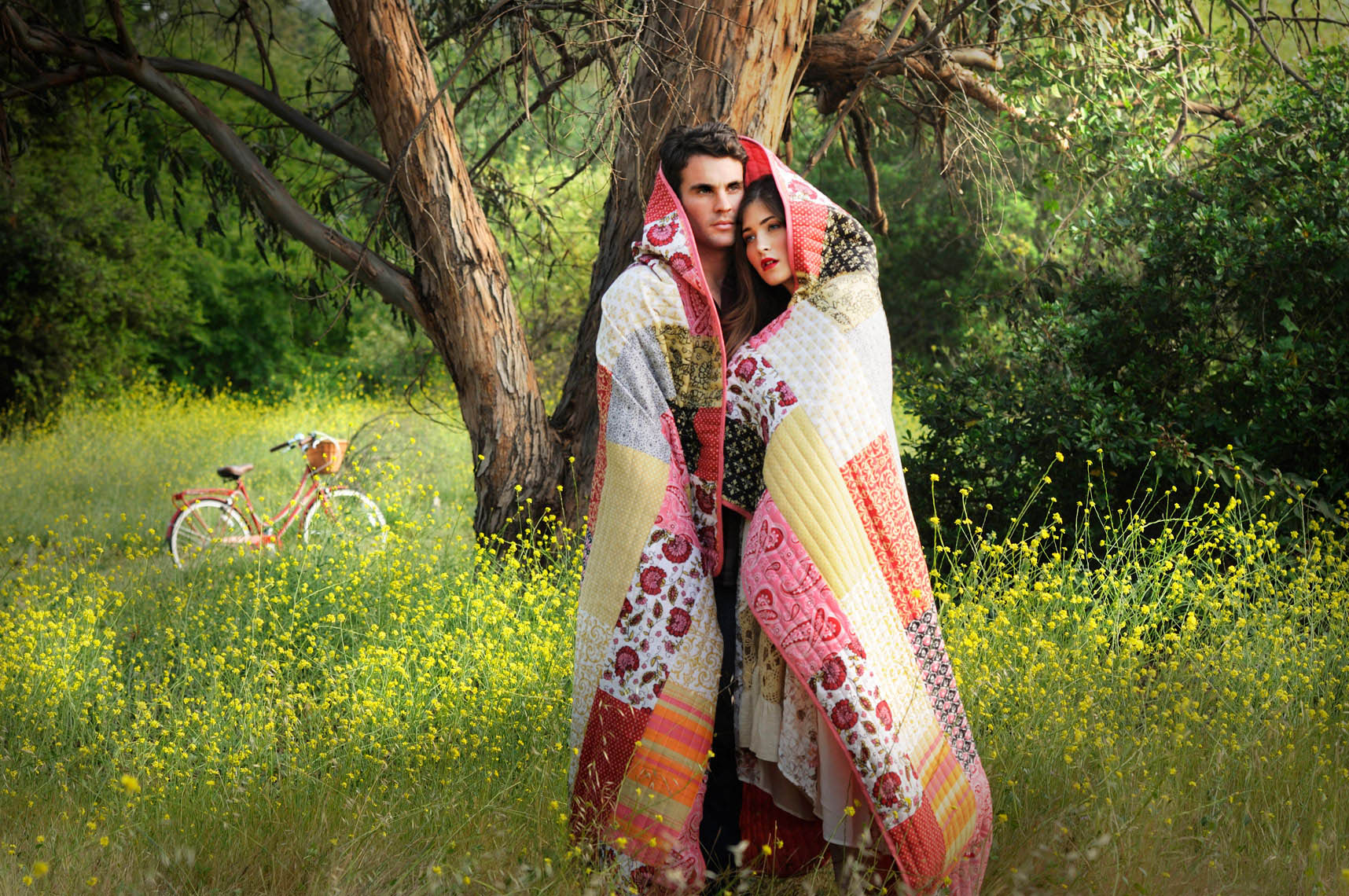 Portrait-of-young-couple-with-blanket-wrapped-around-them-in-a-field-of-yellow-flowers-lifestyle-photographer.