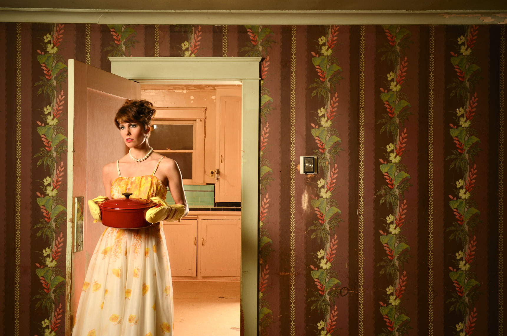 Portrait-of-young-woman-holding-casarole-dish--entering-vintage-dining-room-wearing-vintage-dress-by-Los-Angeles-environmental-portrait-photographer.