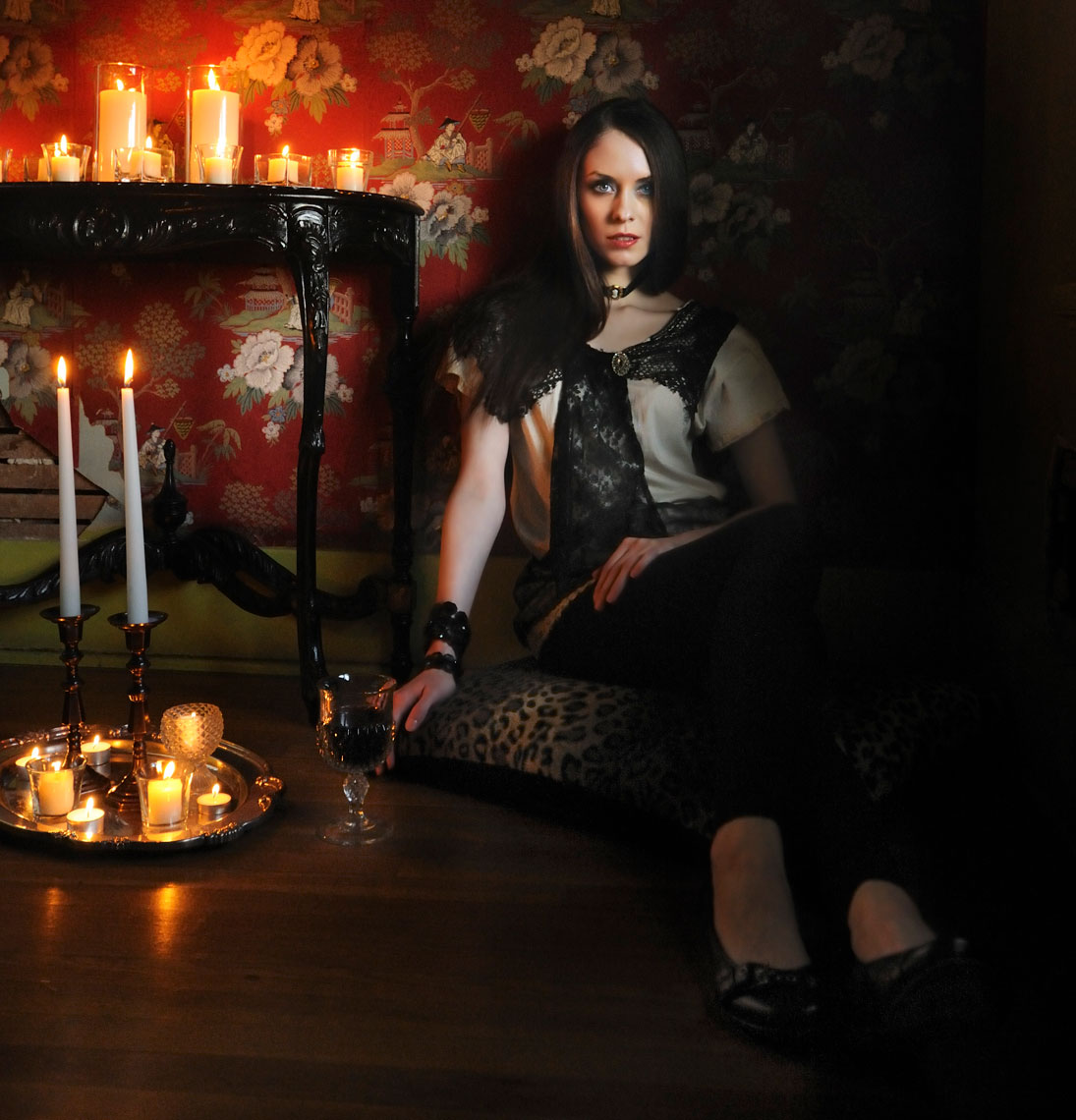 Editorial fashion photography-of-young-woman-seated-with-candles-and-wine