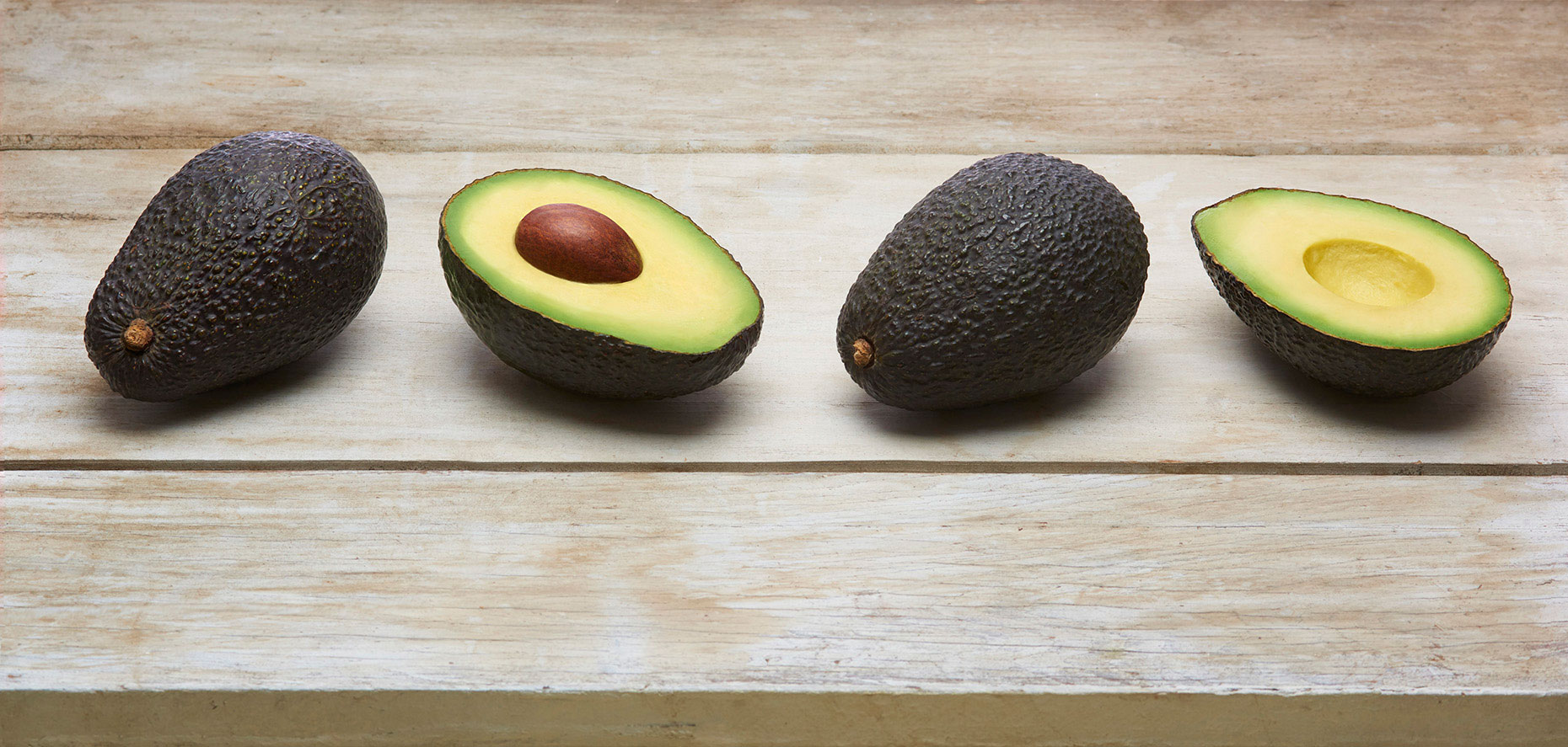 Two-whole-and-one-cut-hass-avocad-on-rustic-white-wood-table-top-by-Joe-Atlas-food-photographer.