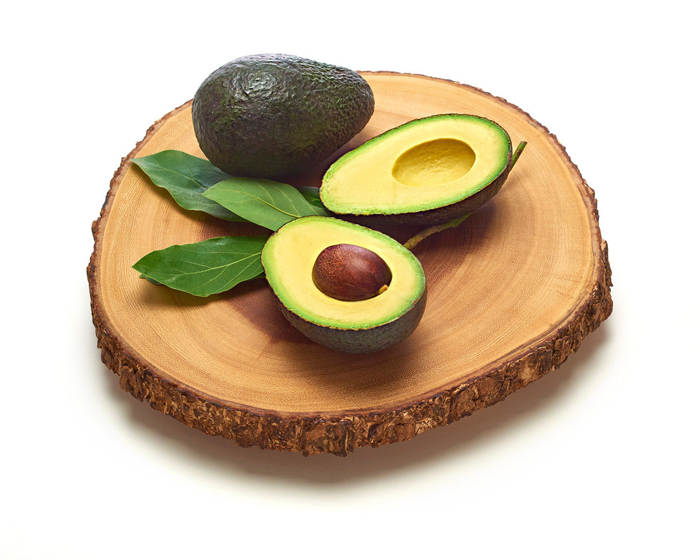 Whole-and-cut-Hass-avocados-on-cutting-board-by-Joe-Atlas-food-photography.