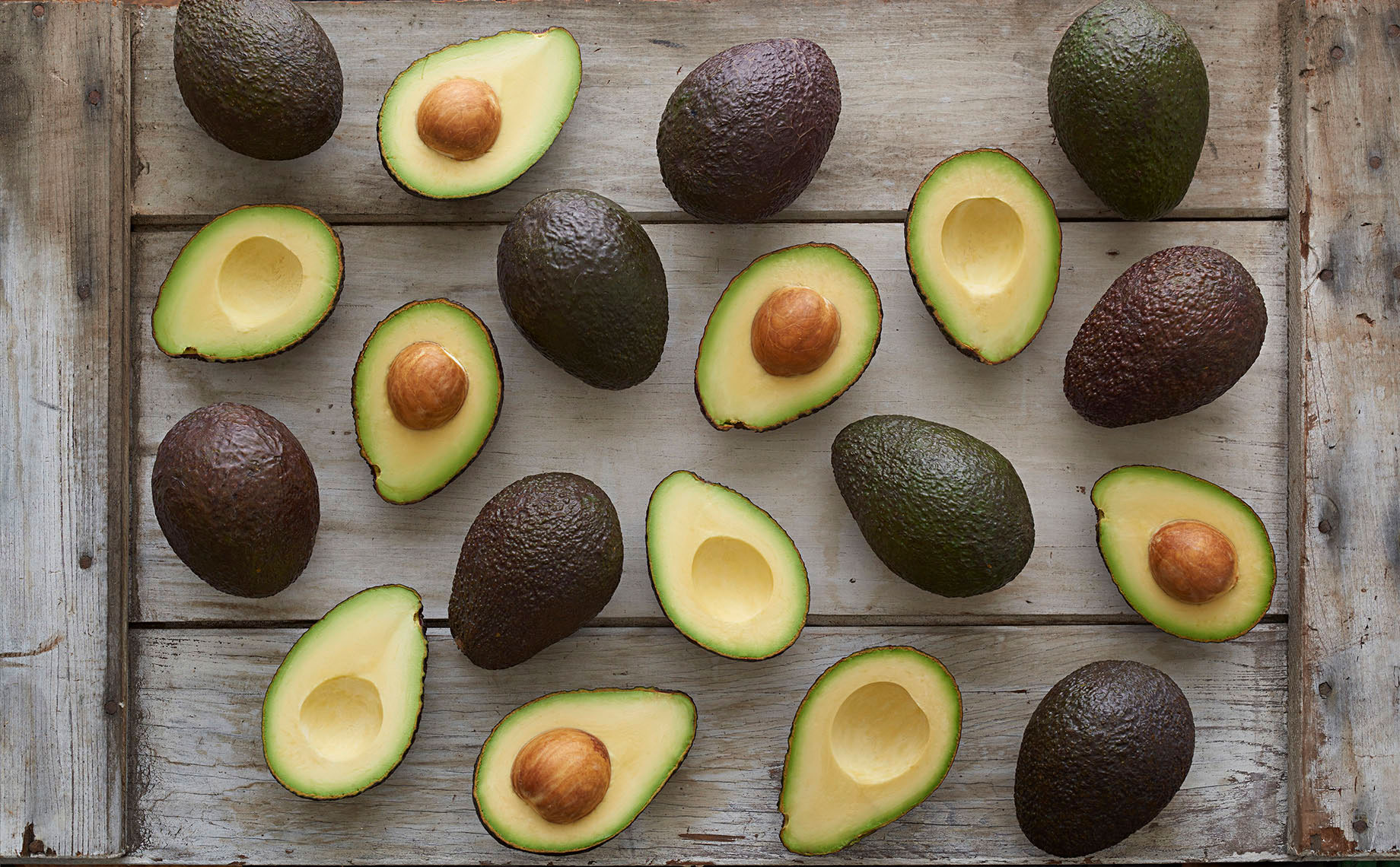 Whole-and-cut-in-half-California-grown-hass-avocados-white-barn-wood-by-Joe-Atlas-food-photography.