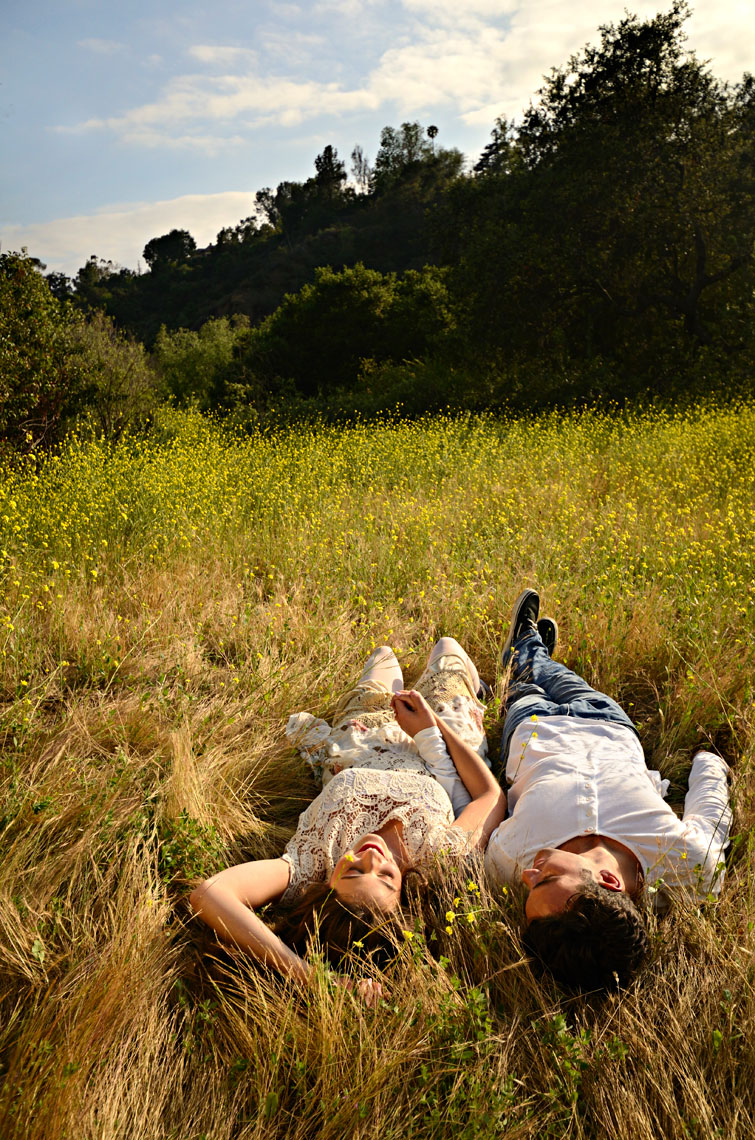 Young-couple-enjoying-a-spring-afternoon-laying-in-grassy-field-with-yellow-wildflowers-by-lifestyle-photographer-Joe-Atlas.