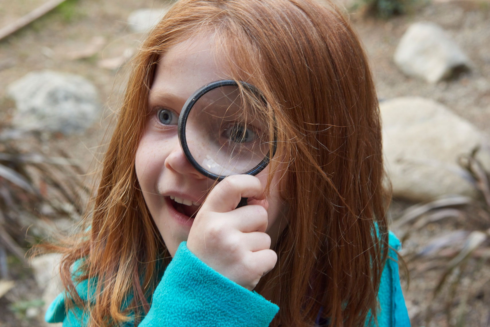 Young_girl_looking_through_magnifying_glass-by-annual-report-photographer-Joe-Atlas.