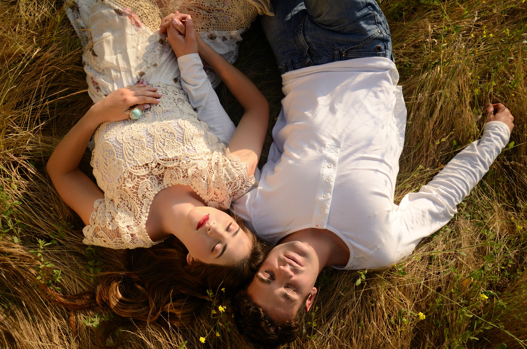 young-romantic-couple-holding-hands-sleeping-in-overgrown-grassy-field-by-lifestyle-photographer-Joe-Atlas.